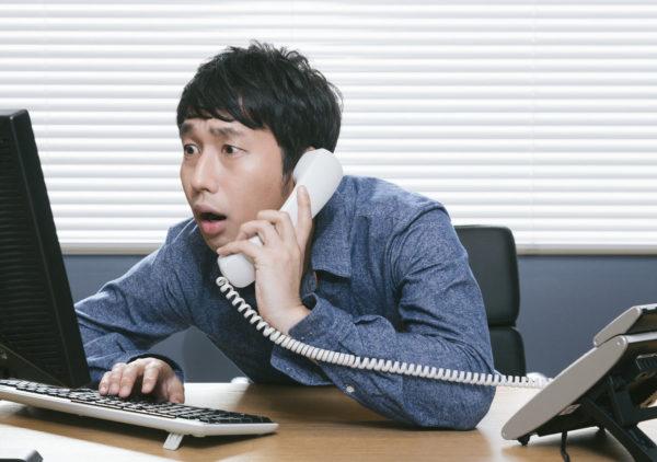 クレーム処理の電話に追われる人